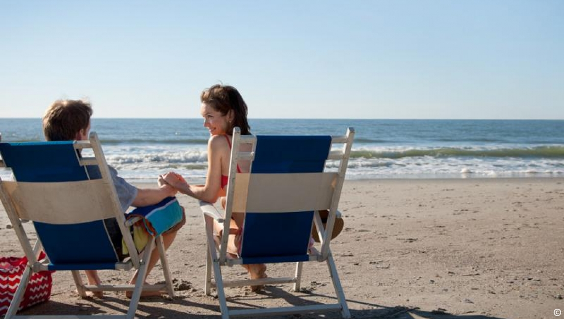 Couple relaxing in beach chairs.